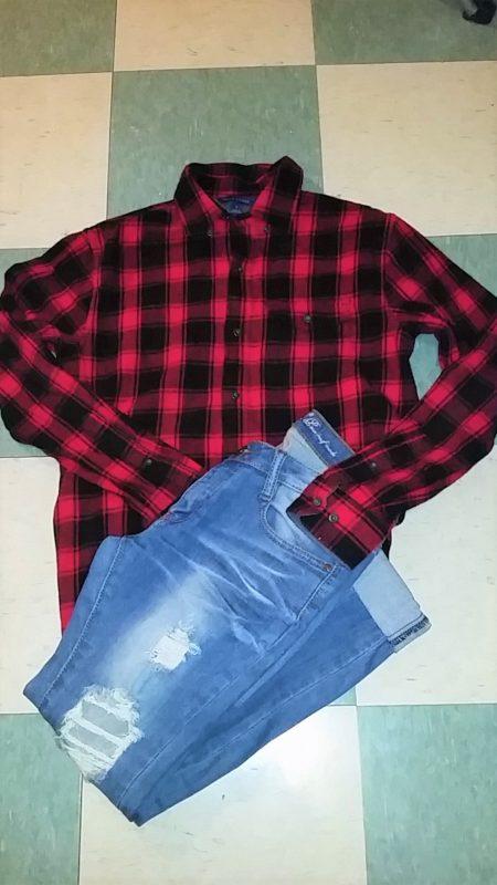 Indumenti iconici della moda grunge: camicia a quadri e jeans strappati.
